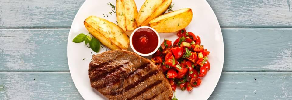 Grillkotelett mit Kartoffelspalten und Tomatensalat